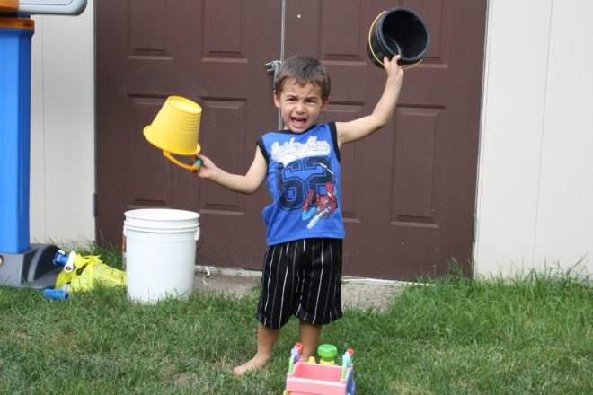 very unhappy boy crying holding buckets