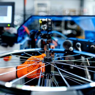 orange gloved hand putting the spokes onto a bike wheel