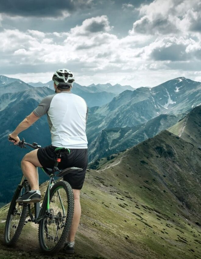 Man on bicycle with view of mountains