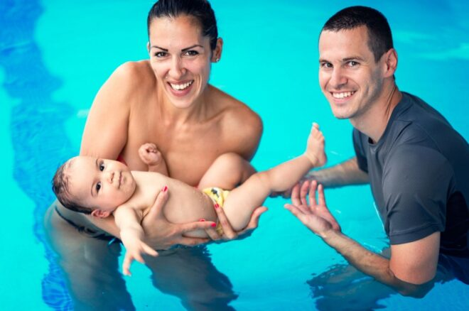 mom and dad with baby in pool