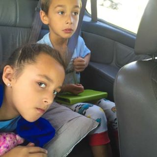 Kids sit in the car in pajamas