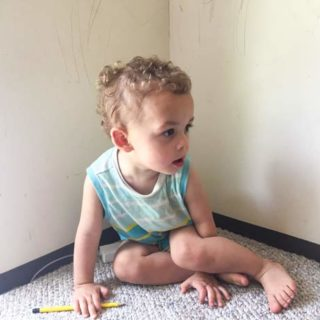 Boy is sitting with a pencil in front of wall on carpet