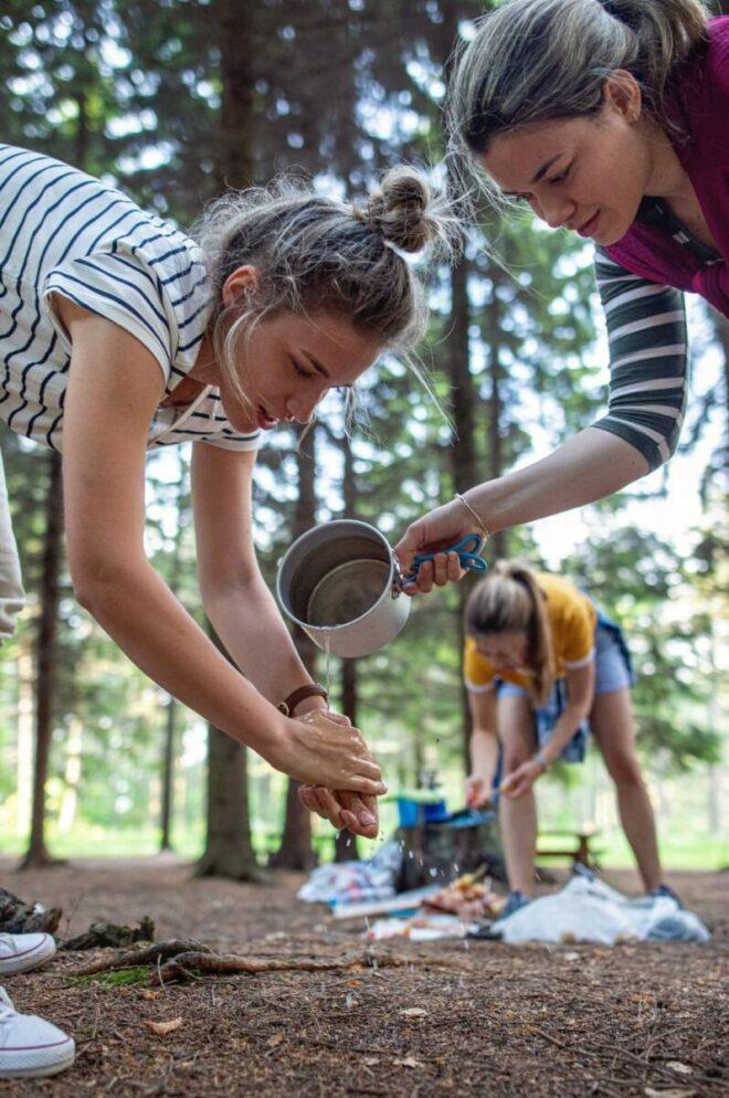 Girl washing hands at camping site