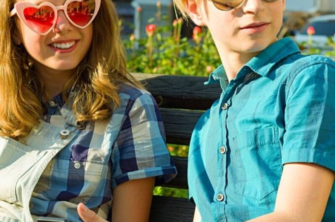 Two teens in sunglasses looking up