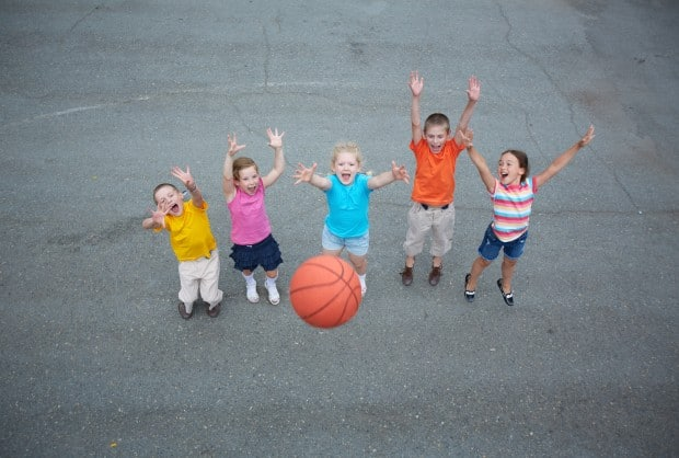 happy-friends-playing-basketball-on-sports-ground
