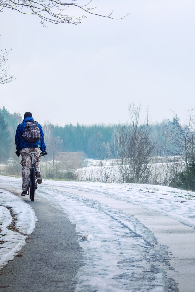 A man cycling away in snow