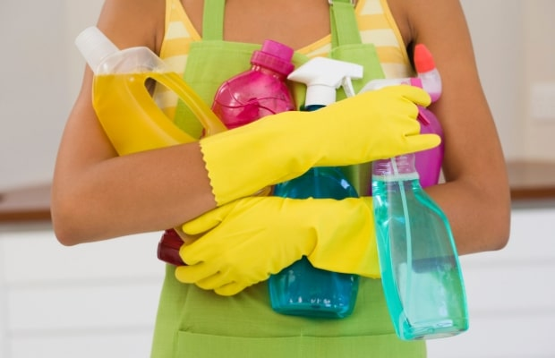 Woman holds cleaning supplies