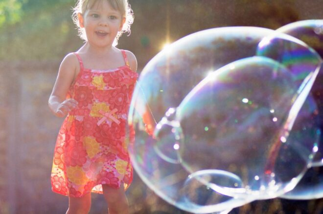 Girl looks at giant bubbles