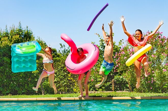 Kids jump in pool with inflatables summer