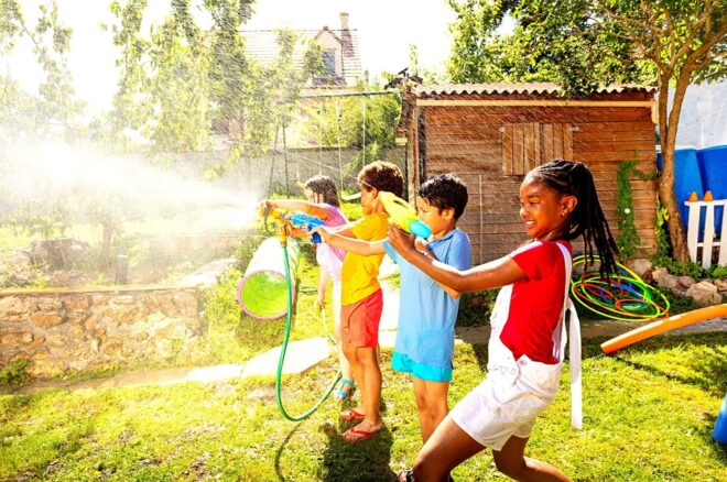 Kids play spray water game outside in summer