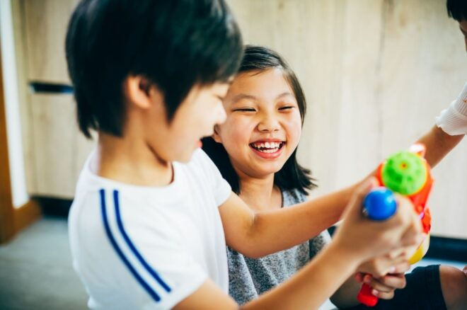 boys and girl laugh and look at spray guns