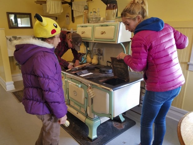 Guide shows to girl old stove at Lafayette Farm at Prophetstown