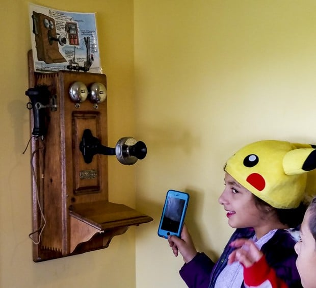 Kids with an old phone and an iphone at Lafayette Farm at Prophetstown