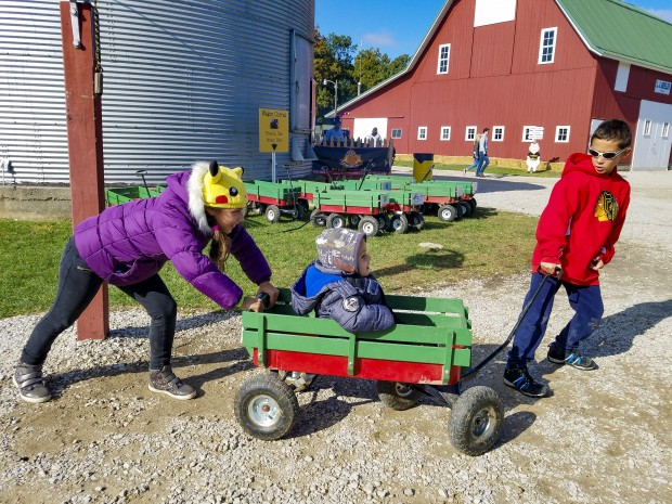 Lafayette Exploration Acres pushing a cart with a child