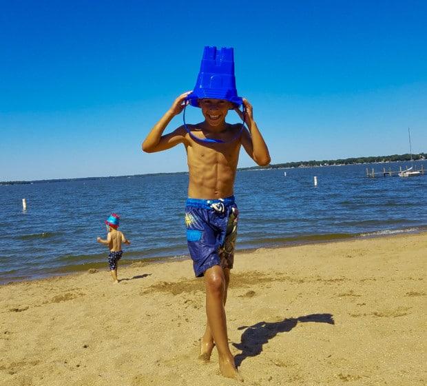 Boy walks with bucket on Clear Lake beach in Iowa