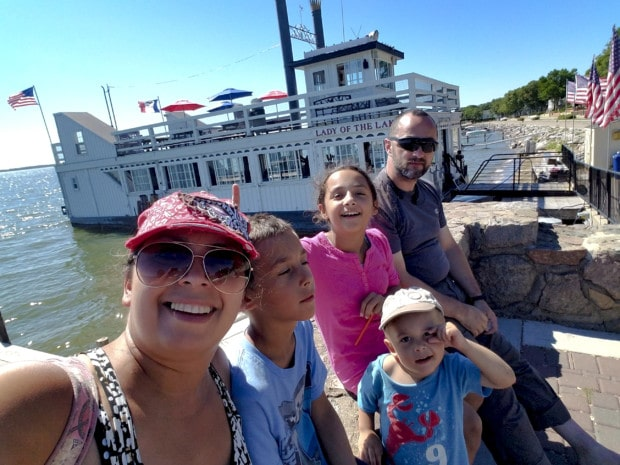 Family is smiling in front of Lady of the Lake in Clear Lake Iowa