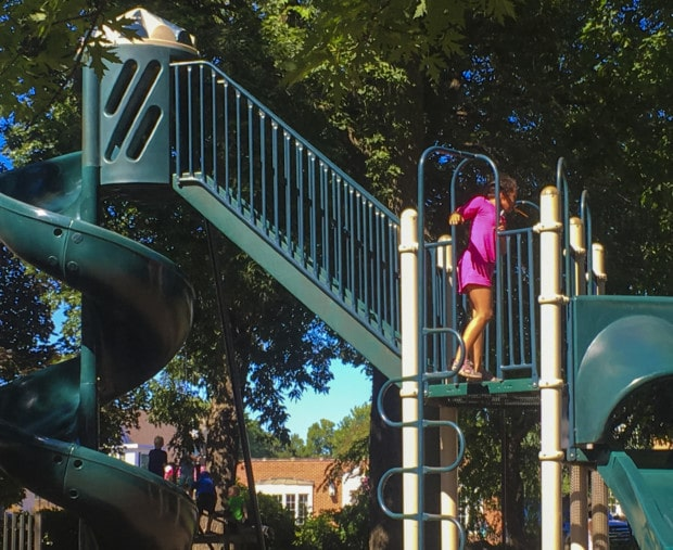 Girl plays on playground in clear lake Iowa