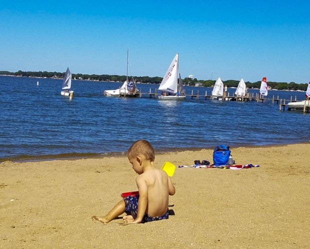 boy is sitting playing with sand on clear Lake Iowa beach