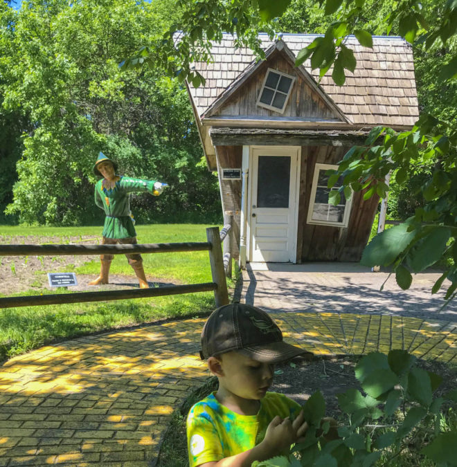 Boy by the scarecrow house at Land of Oz in Storybook Land Aberdeen South Dakota