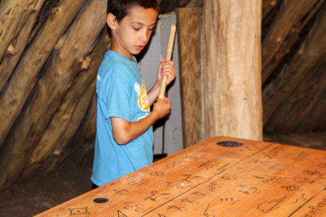 Boy inside of earth lodge in Mandan Native American village at Abraham Lincoln State Park