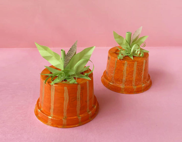 two orange cups with green pieces of paper shaped like a stem, leaves, and vines