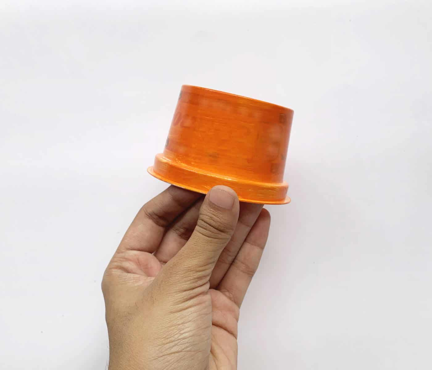 hand holding a short orange cup