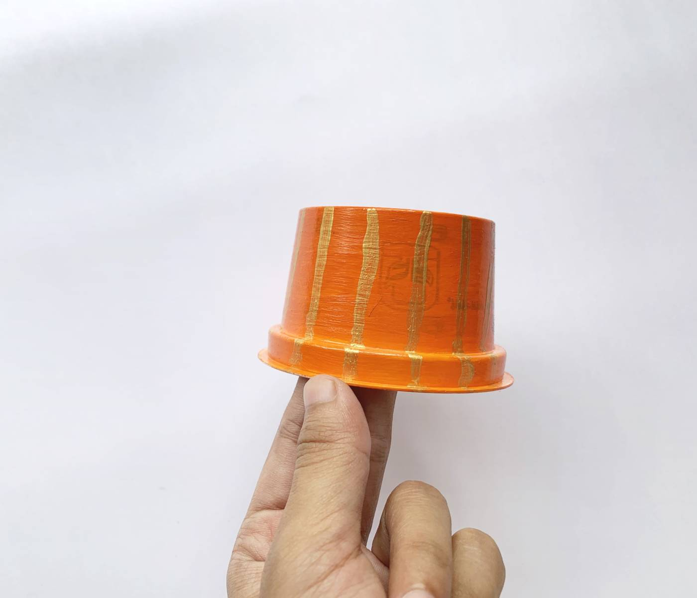 hand holding an orange cup with gold stripes running from the top to the bottom
