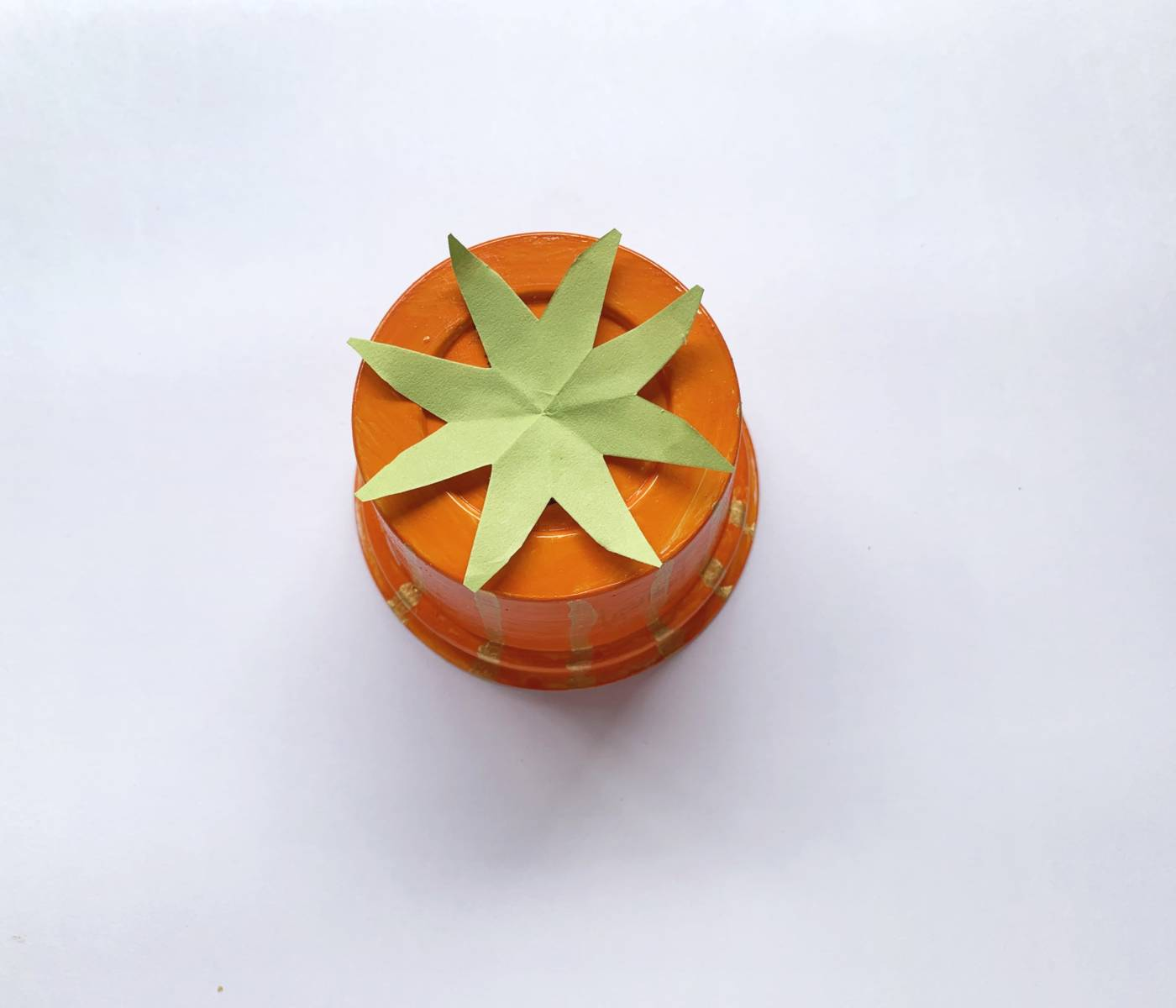 orange cup with a green piece of paper shaped like an eight-pointed star on top
