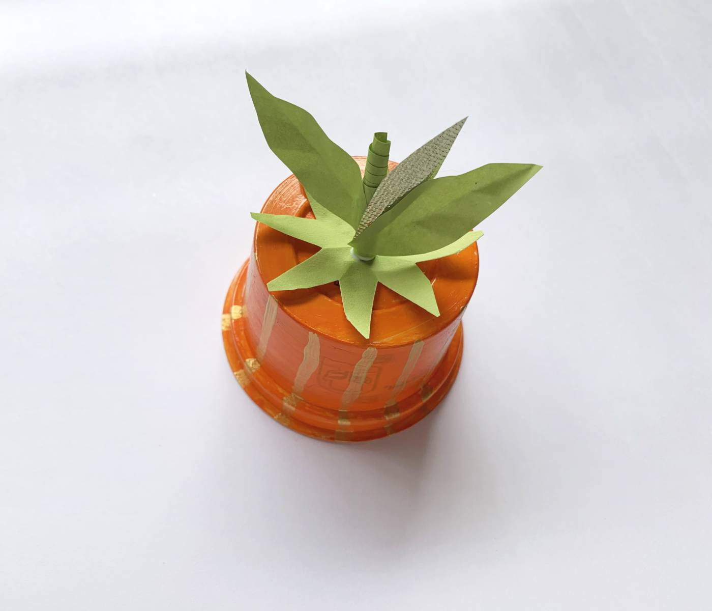 orange cup with fake leaves and a fake stem on top