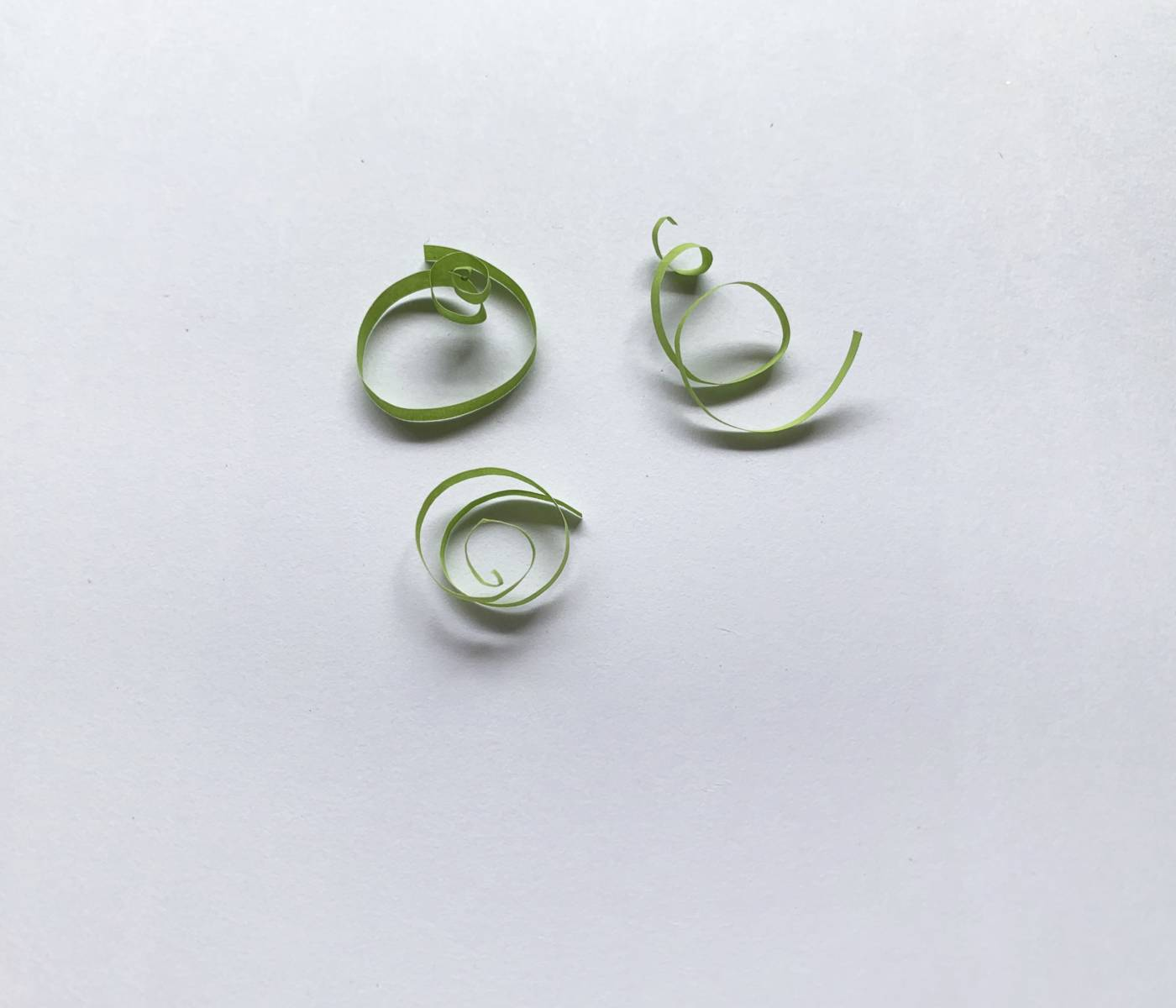 3 green strips of paper shaped like a swirl scattered around