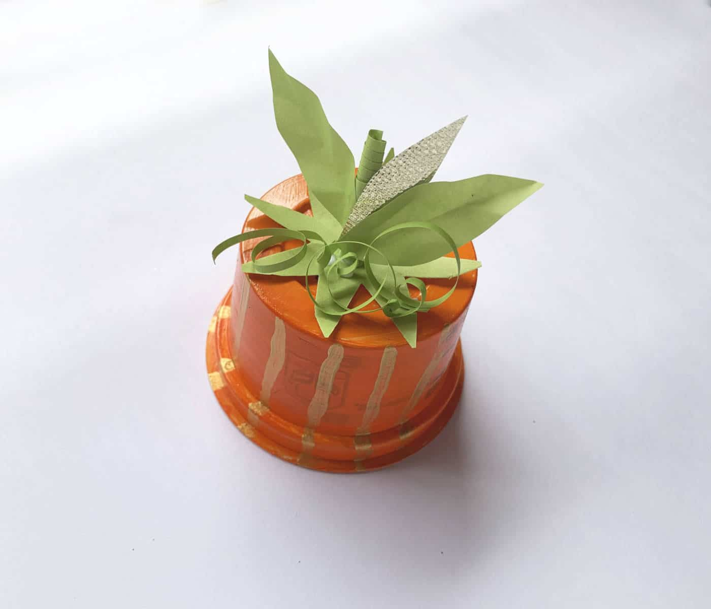 an orange cup with a fake stem, leaves and a fake vine on top