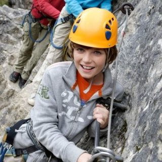 girl wearing a hard hat on a rock wall