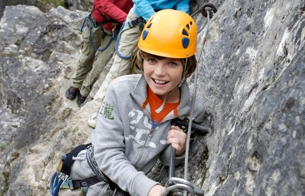 girl wearing a hard hat on a rock wall