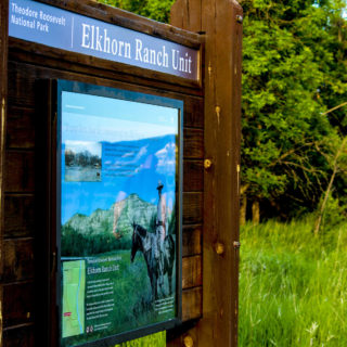 elkhorn ranch unit sign in front of tall, green grass and very green trees