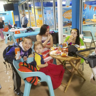 4 kids sitting at a table by the side of a pool with food at the table