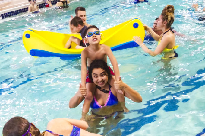 boy on a woman's shoulders in a crowded pool
