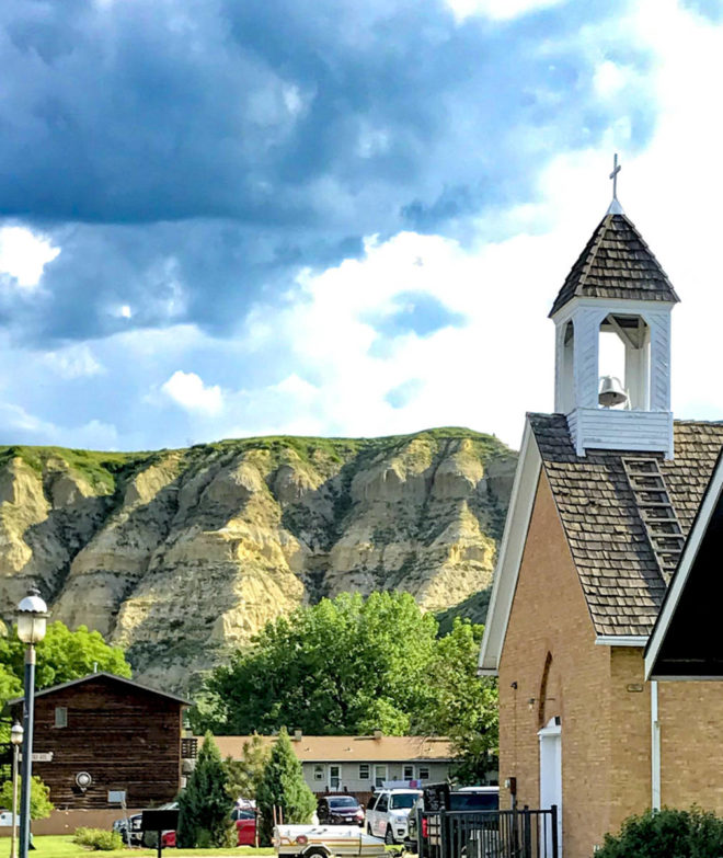 A church in front of mountain in Medora