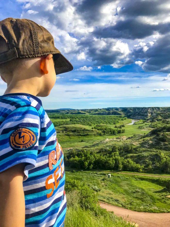 Boy is looking off mountain top onto Dakota mountains