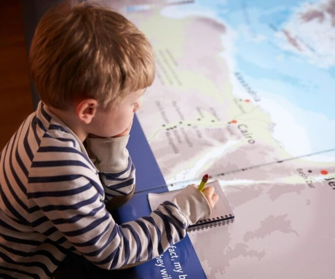 Boy looks over map and taking notes