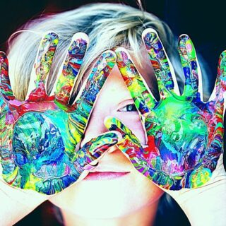 Boys holds colored hands over his face