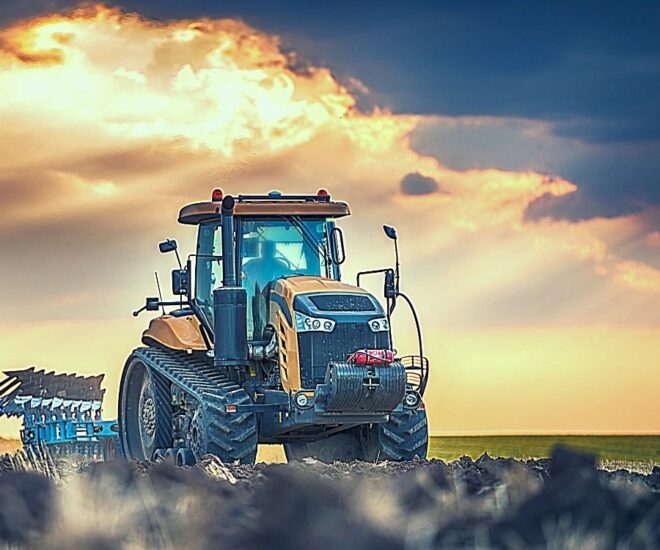 Yellow tractor working in sunset