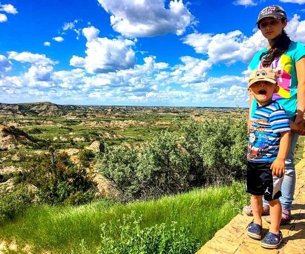 Children standing on top of mountain in Badlands of North Dakota