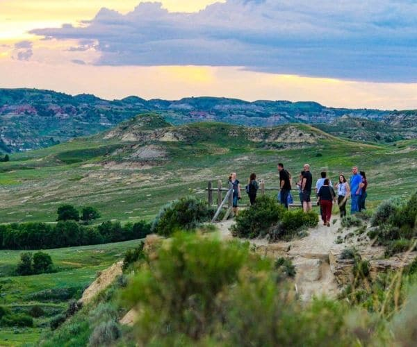 A group of tourists standing on top of mountain in in Theodore Roosevelt's National Park
