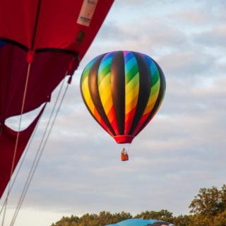 Bright colored air balloon behind another air balloon