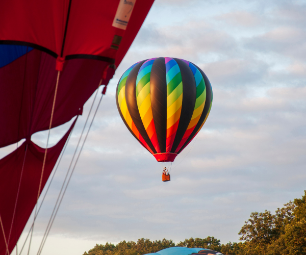 Bright colored air balloon behind another air balloon