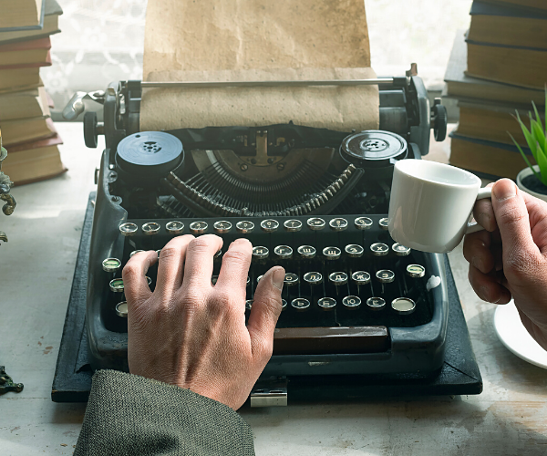 Man typing on typewriter and holding cup of cofffee