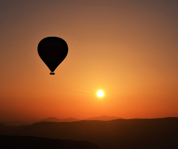 an outline of hot air balloon in sunset skies