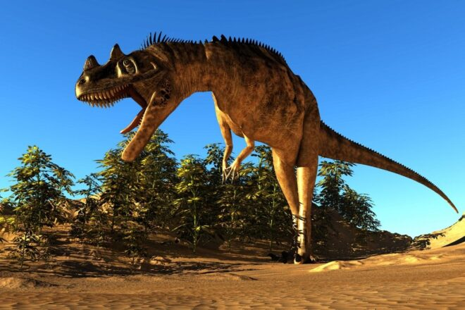 a large dinosaur on a hill with blue skies