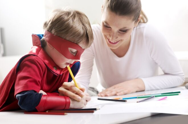 boy dressed in superman costume writes sitting next to his mom