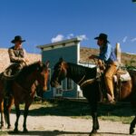 Two Cowboys on horses on town street